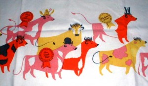 Although harder to find, Keefe did a number of tablecloth designs. This one has Cattle on Parade, with the different beef cows sporting different hats and signs for cuts of beef.