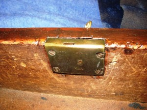 A half mortise lock is implanted part way in the wood but leaves the back plate visible form the inside.