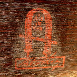 "There is no mistaking Gustav Stickley's unique red decal with the joiner's compass and his trademark quote ""Als ik Kan"" – All I Can Do."