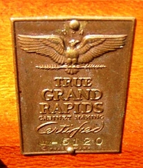 This metal emblem was used by members of the Grand Rapids Furniture Makers Guild, beginning in 1931, to certify each individual piece of furniture by number as having been made by a Guild member.