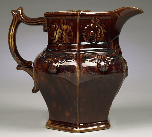 """This wonderful Cincinnati yellow ware paneled water pitcher with Rockingam-type mottled brown glaze on a slip-cast body was made by William Bromley. The pitcher has floral scrollwork decoration and a female with harp below spout. The base has impressed Eagle mark with """"Bromley & Co. Brighton Pottery Cin. Ohio."""""""
