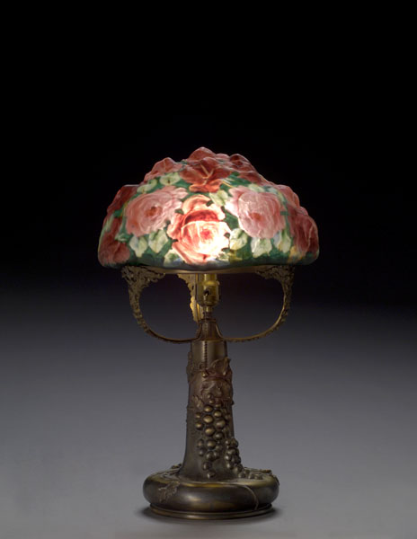 This Pairpoint Puffy closed top 13-inch shade with large red roses and green leaves, supported on an original signed Pairpoint base with molded grapes and leaves, sold for $9,775 (including the buyer's premium).