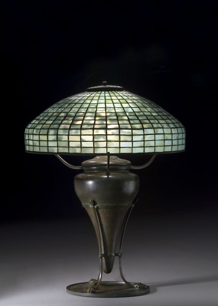 This 18-inch leaded glass geometric shade in blue-green mottled glass, supported by a rare Tiffany bronze base of urn form with paw feet on flat disk, sold for $17,825 (including the buyer's premium) at auction.