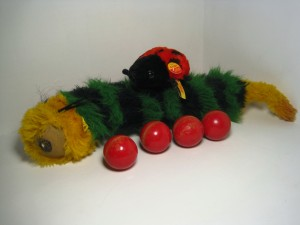 "Steiff's 43-centimeter woven, plush caterpillar on eccentric wheels from 1980-83, accompanied by a modern, 10-cm ""Cappy"" red-and-black, plush ladybug."