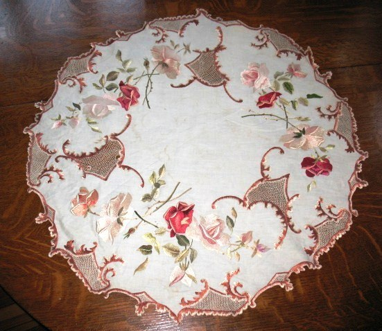 An elaborately embroidered Society Silk table round, measuring 28 inches across, with drawnwork highlights. Dating to the mid-1800s, society silk embroidery began in England. The first public display of this needlework was at the 1876 Centennial in Philadelphia, after which it became very popular in this country.