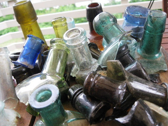 """These colorful bottles would have dated to after 1875 or so, up to about 1900, which is when bottles began to be machine made. These have hand """"tooled"""" lips, where they didn't use a separate piece of glass to form the lip, but instead tooled the top of the bottle."""