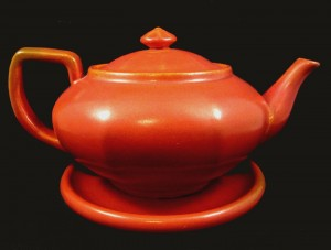 A Toyon red-glazed teapot with a 6-inch rolled-rim plate used as a under plate.