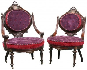 These two chairs from a Renaissance Revival parlor set of the 1870s illustrate the difference in the gentleman's chair (left) and the lady's chair (right) in the overall size, the arrangement of the arms and the size and height of the back. (Flomaton Auction photo)